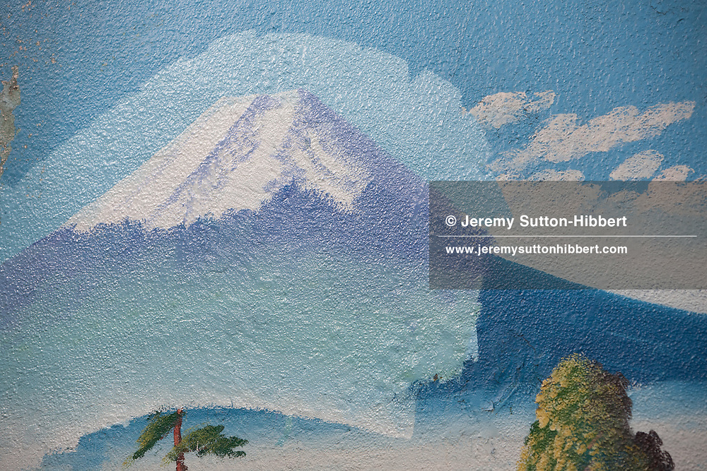 Penki-e (painter who uses paints) Morio Nakajima, and his apprentice of 6 years Mizuki Tanaka, paint a fresh mural of Mount Fuji over the top of an older similar view by painter Hayakawa Toshimitsu, at the 'Moto No Yu' sento (public bath house) in Shinozaki, in eastern Tokyo, Japan, on Thursday 23rd June 2011. Nakajima-san and Kiyoto Maruyama are the two remaining painters of Mt Fuji murals in the Kanto area of Japan. Nakajima-san currently undertakes approximately 70 such mural assignments a year, and they each cost the sento owners approximately JPY 100,000.  Mizuki Tanaka,  a graduate of art history, has been an apprentice to Nakajima-san for 6 years but has not yet progressed to the level where she is allowed to paint the Mt Fuji itself, at present she paints the other background details of the mural but not the mountain itself.