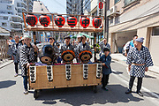 Shinto priests carry a large drum  ahead of mikoshi processions during the Sanja matsuri, Asakusa, Tokyo, Japan. Sunday May 21st 2017 . The Sanja matsuri (Three shrines festival) is one of the biggest Shinto festivals in Japan. It takes place for 3 days around the third weekend of May and features over 100 large and small mikoshi, or portable shrines, which are paraded around the streets of the historic Asakusa district in Tokyo. to bring blessings and good luck on the inhabitants. The events attracts up to 2 million visitors each year.
