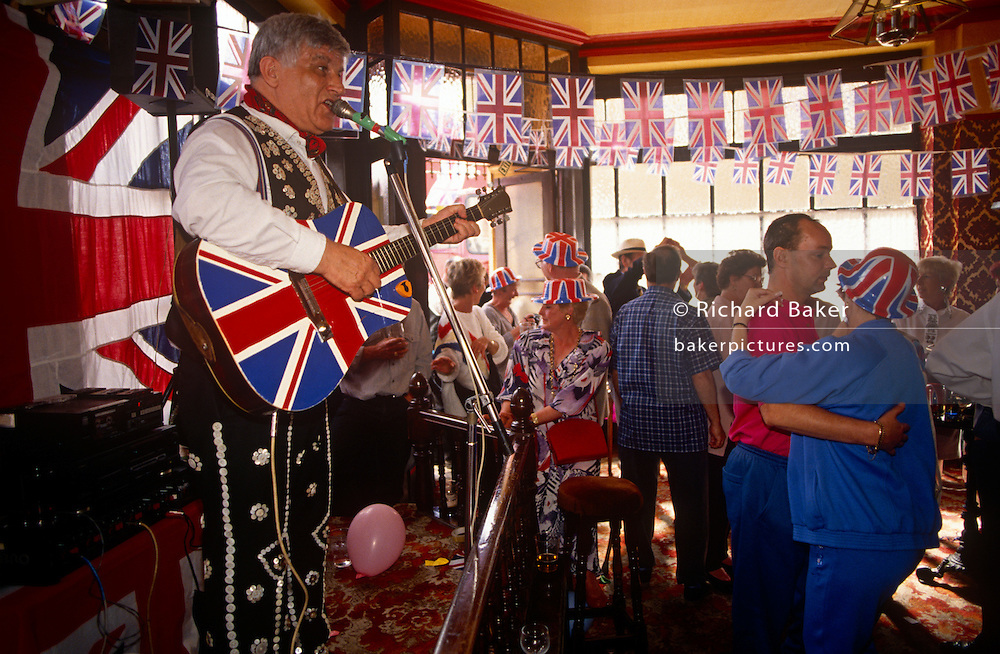 East end Londoners dance in a wave of nostalgia as they gather in their local east end pub in east London, England. Union Jack flags are everywhere - and even on a singer's acoustic guitar - as they remember the 50th anniversary of VE (Victory in Europe) Day on 6th May 1995. In the week near the anniversary date of May 8, 1945, when the World War II Allies formally accepted the unconditional surrender of the armed forces of Germany and peace was announced to tumultuous crowds across European cities, the British still go out of their way to honour those sacrificed and the realisation that peace was once again achieved. Street parties now - as they did in 1945 - played a large part in the country's patriotic well-being.