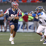 Paul Rabil #99 of the Boston Cannons keeps the ball from Mason Poli #55 of the Charlotte Hounds during the game at Harvard Stadium on May 17, 2014 in Boston, Massachuttes. (Photo by Elan Kawesch)