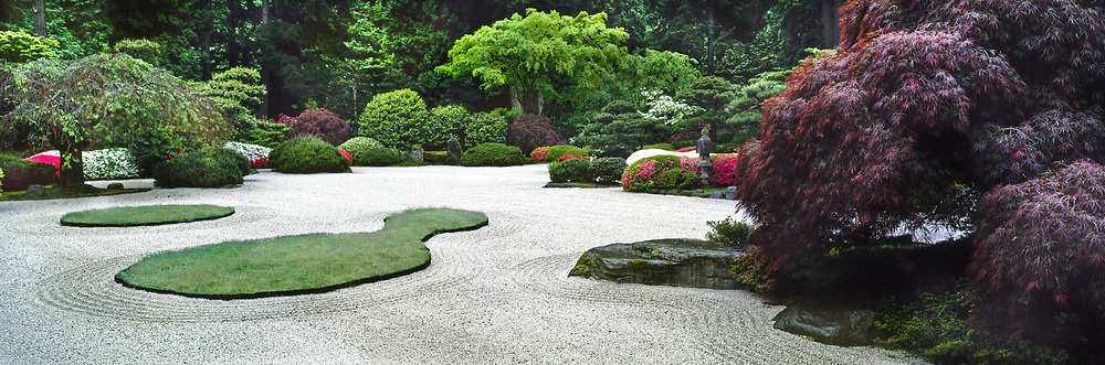 Japanese Garden, Portland. Oregon, USA.<br /> Design by Professor Takuma Ton.<br /> Raked gravel, boulders, grass islands, clipped shrubs including flowering Azalea, stone ornament &amp; trees including Acer dissectum (Japanese maple), Pinus &amp; Prunus (cherry).