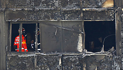 Fire service personnel survey the damage inside Grenfell Tower in west London after a fire engulfed the 24-storey building on Wednesday morning.