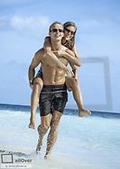 Junges Paar am Strand, er nimmt Freundin Huckepack (model-released)