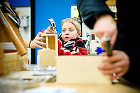 JEROME A. POLLOS/Press..J.T. Hansen, a preschool student from the North Idaho College Children's Center, focuses all his attention at hammering a nail into his miniature toolbox he crafted with the assistance of a Lakes Middle School student Wednesday.