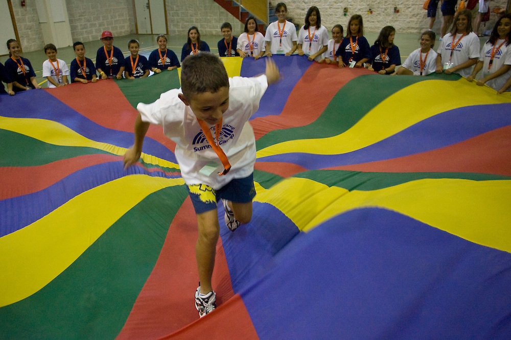 "(El Puerto de Santa Maria, Spain - July 18, 2010) - A camper chases the ""mouse"" during an arrivals game in the gym on the first day of Family Camp 2 in El Puerto. ..Photo by Will Nunnally / TECS"