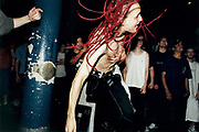 Young man with red dreads dancing in front of a group of people.