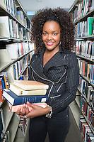 Female University student holding books in library, portrait