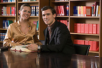 Young man and woman studying at desk in library portrait