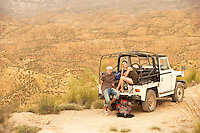 Couple sitting at back of four wheel drive car on edge of cliff in desert