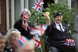 @Licensed to London News Pictures 08/05/2020. Maidstone, UK. Residents wave Union Jacks to commemorate VE75 Day at Queen Elizabeth Court in the Royal British Legion village in Aylesford, Kent. RBLI also wanted to use Two Minute Silence to honour the service and sacrifice of the Second World War generation and reflect on the devastating impact Covid-19 has had on so many lives across the world.  Photo credit: Manu Palomeque/LNP