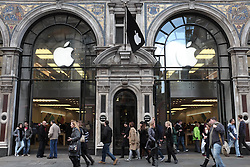 © Licensed to London News Pictures. 27/10/2013. London, UK. Shoppers walk past Apple's flagship store on Regent Street - Apple is to announce its Q4 Fiscal Results tomorrow.  . Photo credit : Richard Isaac/LNP