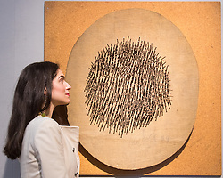 Bonhams, London, March 6th 2017. Fine art auctioneers Bonhams hold a preview in London  for their upcoming Post-War and Contemporary Art Sale which takes place on March 8th 2017. PICTURED: A woman examines Günther Uecker's 'Oval' which together with another of his pieces, 'Vogel' are expected to fetch between £400,000 - 650,000 each.