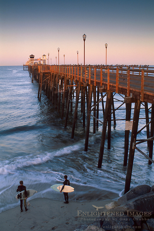 Surfers watch the waves on a calm morning at wooden Oceanside Pier, San Diego County, California