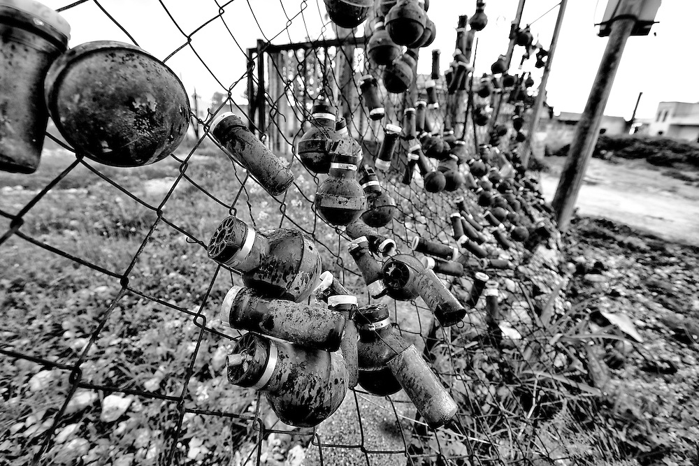 Villagers decorate a fence with used tear gas canisters and concussion grenades. Nabi Saleh. Mar. 25, 2011. West Bank, Palestine.
