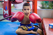 23 DECEMBER 2014 - BANGKOK, THAILAND: A boy waits to get into the ring in the Kanisorn gym in Bangkok. The Kanisorn boxing gym is a small gym along the Wong Wian Yai - Samut Sakhon train tracks. Young people from the nearby communities come to the gym to learn Thai boxing. Muay Thai (Muai Thai) is a mixed martial art developed in Thailand. Muay Thai became widespread internationally in the twentieth century, when Thai boxers defeated other well known boxers. A professional league is governed by the World Muay Thai Council. Muay Thai is frequently seen as a way out of poverty for young Thais. Muay Thai professionals and champions are often celebrities in Thailand.     PHOTO BY JACK KURTZ