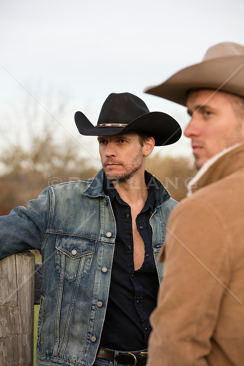 two cowboys on a ranch outdoors
