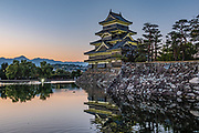 "Lighted southeast faces of Matsumoto Castle, built 1592-1614, backed by twilight over Japan Alps, in Nagano Prefecture. The castle was built from 1592-1614 in Matsumoto. Matsumoto Castle is a ""hirajiro"" - a castle built on plains rather than on a hill or mountain, in Matsumoto. Matsumotojo's main castle keep and its smaller, second donjon were built from 1592 to 1614, well-fortified as peace was not yet fully achieved at the time. In 1635, when military threats had ceased, a third, barely defended turret and another for moon viewing were added to the castle. Interesting features of the castle include steep wooden stairs, openings to drop stones onto invaders, openings for archers, as well as an observation deck at the top, sixth floor of the main keep with views over the Matsumoto city."