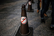 "A sign urges visitors to ""manner up"" in English and with graphics showing a hand littering in the Gion entertainment and geisha quarter.  Kyoto, Japan."