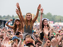 © Licensed to London News Pictures. 12/06/2015. Isle of Wight, UK.   Festival goers on their friends shoulders watch You Me at Six  perform at Isle of Wight Festival 2015 on Friday Day 2 on the main stage.  Yesterday the weather was hot and Sunny.  Today there has been torrential rain this afternoon. This years festival include headline artists the Prodigy, Blur and Fleetwood Mac.  Photo credit : Richard Isaac/LNP