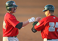 TinCaps third baseman Justin Baum (14) bumps fists with first base coach Tom Tornincasa (24) after a walk to load the bases in the second inning of game three of the Midwest League Championship at Community Field in Burlington, Iowa on September 17, 2009.