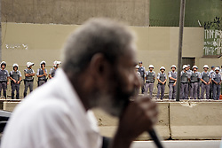 An inhabitant of the Prestes Maia occupation, speeching in a day of protests while military police watch, in front of the occupation. (February, 2006)