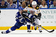 Tampa Bay Lightning's Benoit Pouliot, left, and Boston Bruins' Brad Marchand battle for a puck during the third period of an NHL hockey game Thursday, Feb. 21, 2013, in Tampa, Fla. The Bruins won 4-2. (AP Photo/Mike Carlson)
