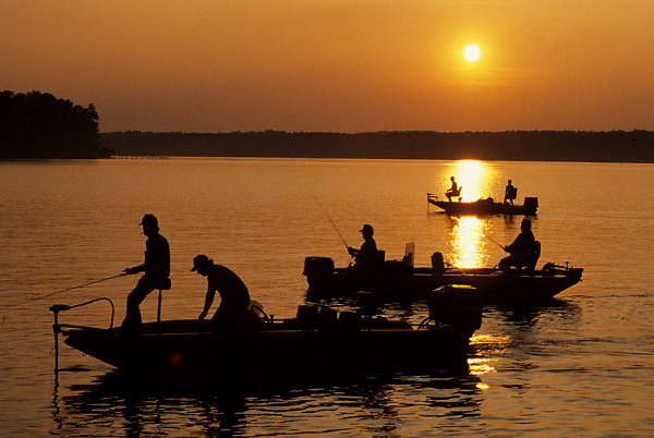 Stock photo of a silhouette of a group of bass fishermen in fishing boats on Toledo Bend lake at sunset.
