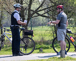 © Licensed to London News Pictures. 11/04/2020. London, UK. A Police cyclists patrolling Richmond Park question a cyclist where a cycling ban is in place for adults in the park during the coronavirus disease pandemic. Londoners have been told to stay at home and only leave homes to exercise or when absolutely essential in an attempt to fight the spread of COVID-19 as temperatures for the Easter Bank holiday weekend are expected to reach 26c. Photo credit: Alex Lentati/LNP