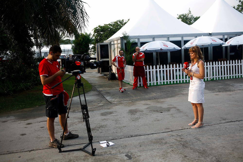 Television crews do reporting from the Paddock area at the Malaysian Formula One Grand Prix in Sepang, Malaysia, Thursday, April 7, 2011.