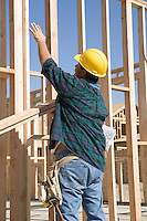 Construction Worker standing in front of house construction and gesturing