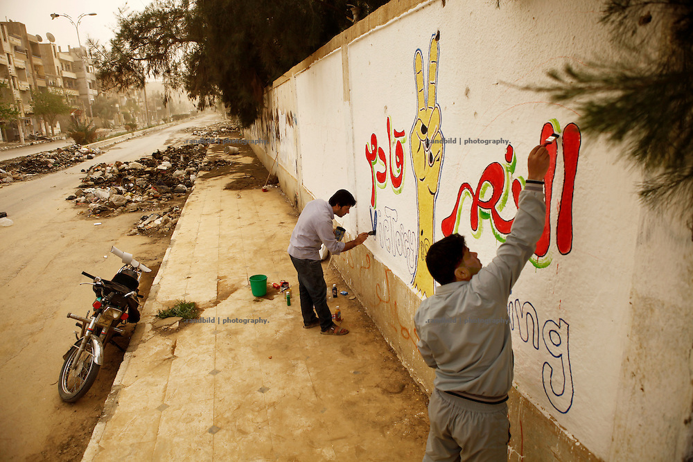 Painters place a graffiti (Victory is comming) at a wall of the former college. They risking much as this road is knows as a sniper alley where Assad lyalist targeting bypassers. Residents of eastern syrian town Deir az-Zor joined arab spring protests against the regime of Bashar al-Assad from its early beginning in March 2011. Since summer 2012 the town with few hundred thousand inhabitants is embattled between the Syrian Army and different opposing rebel groups like Free Syrian Army and Jabhat al-Nusra. Deir az-Zor is target to constant shelling by artillery, war planes and short range missiles. Almost 70 percent of the town is rebel held while government forces remain in control over some residental areas and a strategic important airport. Deir az-Zor is widely damaged and some areas almost totally destroyed by fierce and long lasting battles. All direct road connections to Deir az-Zor are cut and fighters and returning residents as well depend on one provisional supply line across the Euphrates river which is regularly targeted by government snipers.