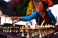 A Nepali lady arranges butter lamps according to prayers sold and prayers to be sold in a stall in the Boudhanath Stupa, thus asking for health, good luck and blessings, in Kathmandu, Nepal.