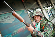 14 MAY 2010 - BANGKOK, THAILAND: A Thai soldier with a shotgun advances down Rama IV Road in Bangkok Friday. Thai troops patrol Rama IV Road in Bangkok Friday after clearing about 50 meters of the road of anti-government protesters who attacked the troops with rocks and home made explosives. Thai troops and anti government protesters clashed on Rama IV Road Friday afternoon in a series of running battles. Troops fired into the air and at protesters after protesters attacked the troops with rocket and small homemade explosives. Unlike similar confrontations in Bangkok, these protesters were not Red Shirts. Most of the protesters were residents of nearby Khlong Toei slum area, Bangkok's largest slum area. The running battle went on for at least two hours.   PHOTO BY JACK KURTZ