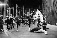 Birmingham Royal Ballet in a warm up class on stage during a regional tour in Plymouth, UK. Sets in the background include Giselle's House and the grid for David Bintley's Shakespeare Suite. Principal dancer, Cathy Batchelor,  is centre in an arabesque.