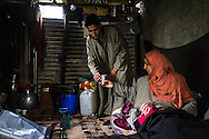Shugufta, 29, and her husband, goes about their daily lives in their temporary shelter in Narbal village, Jammu and Kashmir, India, on 24th March 2015. When the floods hit in the middle of the night, Shugufta and her family had to walk 5 miles to find shelter. Save the Children supported the family with shelter kits, blankets, hygiene items, food and tarpaulin, which they have used to build a temporary shelter next to their crumbled home. Photo by Suzanne Lee for Save the Children