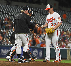 June 19, 2017 - Baltimore, MD, USA - Baltimore Orioles manager Buck Showalter, left, relieves starting pitcher Dylan Bundy, right, in the fifth inning against the Cleveland Indians on Monday, June 19, 2017 at Oriole Park at Camden Yards in Baltimore, Md. (Credit Image: © Kenneth K. Lam/TNS via ZUMA Wire)