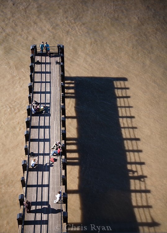 Pier and shadow in front of the Oxo Building, River Thames, London, United Kingdom