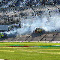 Parker Kligerman (30) gets airborne as he is involved in a crash with Ryan Truex (83), Paul Menard (27), and Dave Blaney (77) during the  56th Annual NASCAR Daytona 500 practice session at Daytona International Speedway on Wednesday, February 19, 2014 in Daytona Beach, Florida.  (AP Photo/Alex Menendez)