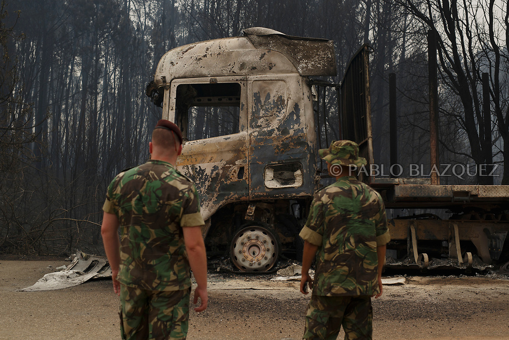 LEIRIA, PORTUGAL - JUNE 19:  Portuguese soldier check the area as they stand next to a track after a wildfire took dozens of lives on June 19, 2017 near Castanheira de Pera, in Leiria district, Portugal. On Saturday night, a forest fire became uncontrollable in the Leiria district, killing at least 62 people and leaving many injured. Some of the victims died inside their cars as they tried to flee the area.  (Photo by Pablo Blazquez Dominguez/Getty Images)