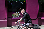 As the UK's Coronavirus death toll during the government's social distancing lockdown, rose by 384 to 33,998, and the R rate of infection is reported to be between 0.7 and 1.0, a cyclist rides past a fallen poster with an ironic metaphor of a disastrous Covid spring, in the window of a food business in the City of London, the capital's financial district, on 15th May 2020, in London, England.