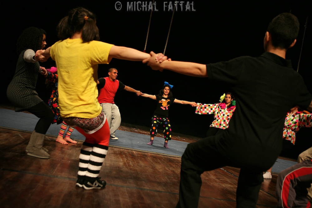 "The Palestinian Circus School members stretch before performing the show ""Circus behind the wall"" in Ramallah, November 20, 2009.The circus group was established in 2006, in order to give a new way of expression for Palestinians, and a new way to deliver the idea of resistance to the occupation. This performance is based on the life of Palestinians behind the separation wall. Photo by Michal Fattal/backyard"