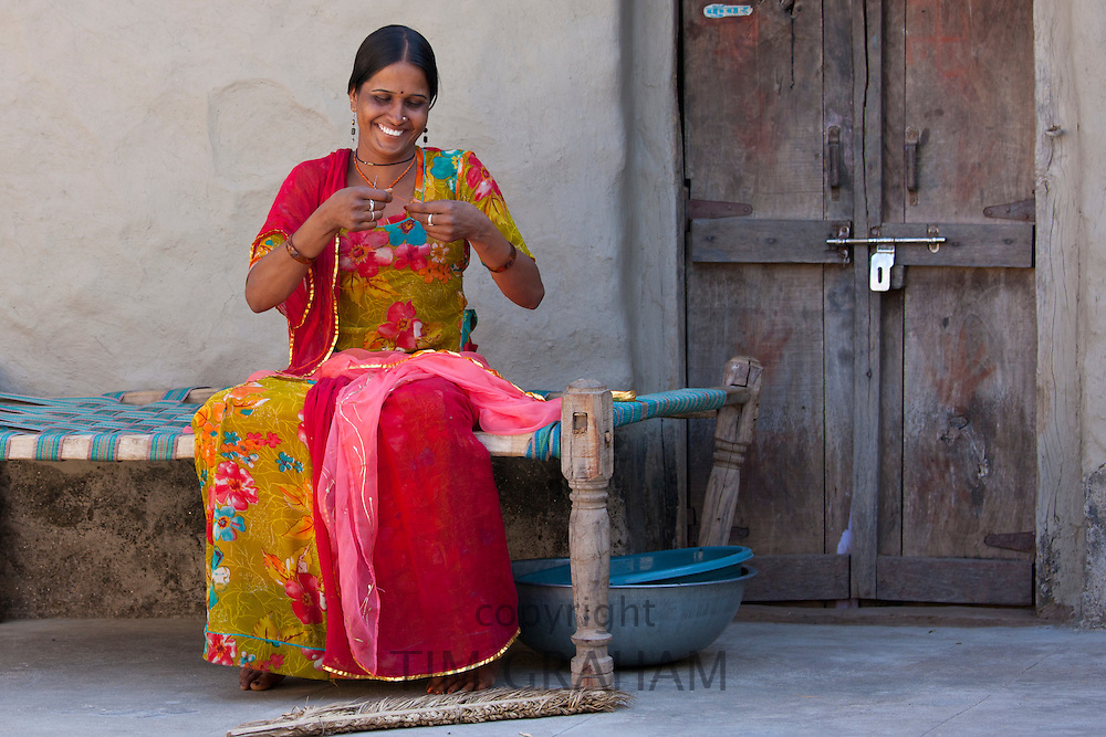 Young Indian Hindu girl sewing bridal veil at home in Tarpal in Pali District of Rajasthan, Western India