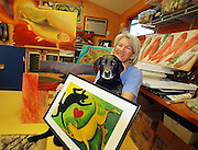 """PARTNERS IN ART--South Carroll artist Melinda Byrd is known for her whimsical images.of fish and dogs.  Melinda draws some of her inspiration from.her """"Lab Assistant"""", """"Hooper""""--a black lab who is also a fine lap dog."""