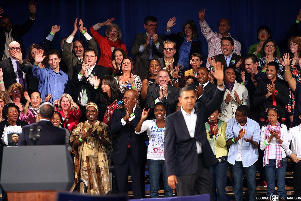 Governador Deval Patrick (a la izquierda y despalda) saluda al publico detras del podium; mientras enfrente el presidente Barak Obama (de frente)se despide de unos 10,000 entusiasta participantes, durante el rally por la reeleción de Sr. Patrick en el Hynes Convention Center, en Boston. <br /> <br /> El discurso del Gov. Patrick fue considerados por algunos medios como un de us mejores.<br /> <br /> Obama estaba algo afonico -lo que puediera ser atribuido a su aprenda agenda eletoral para ayudar al PD. <br /> <br />  La audiencia se delito de tener al presidente otra vez en Boston.