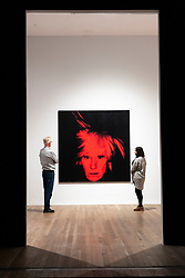 © Licensed to London News Pictures. 10/03/2020. Gallery staff view a self portrait  artwork,1986, by artist Andy Warhol at an exhibition showing at the Tate Modern. London, UK. Photo credit: Ray Tang/LNP