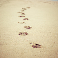 Footprints in sand retro picture with vintage nostalgic tone. Photo was taken in Huntington Beach, Orange County, California. Image Copyright © Paul Velgos All Rights Reserved.