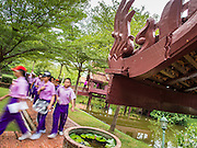 16 JULY 2014 - SAMUT PRAKAN, SAMUT PRAKAN, THAILAND: Thai students on a field trip walk through the grounds of Ancient Siam. Ancient Siam is a historic park about 200 acres (81 hectares) in size in the city of Samut Prakan, province of Samut Prakan, about 90 minutes from Bangkok. It features historic recreations of important Thai landmarks and is shaped roughly like the country of Thailand.      PHOTO BY JACK KURTZ