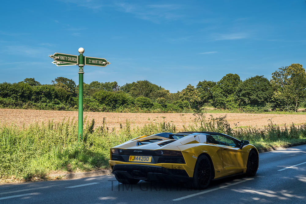 Yellow Lamborghini sports car, Jersey registered number plate, driving past signpost St Martins and Trinity Church in Jersey, Channel Isles