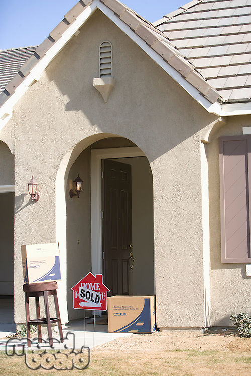 Facade of house with sold sign and few cardboard boxes
