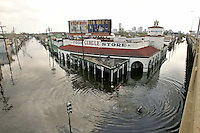 A man swims by the Circle Food Store with the skyline in the background in flooded New Orleans August 30, 2005. Floodwaters engulfed much of New Orleans on Tuesday as officials feared a steep death toll and planned to evacuate thousands remaining in shelters after the historic city's defenses were breached by Hurricane Katrina.
